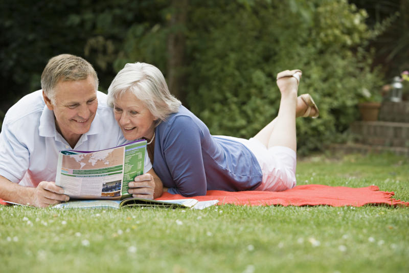 Senior couple lying on blanket on grass reading pamphlet
