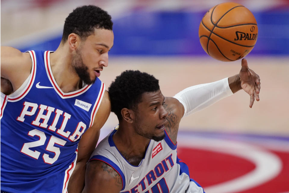 Detroit Pistons guard Josh Jackson (20) loses control of the ball next to Philadelphia 76ers guard Ben Simmons (25) during the second half of an NBA basketball game, Monday, Jan. 25, 2021, in Detroit. (AP Photo/Carlos Osorio)