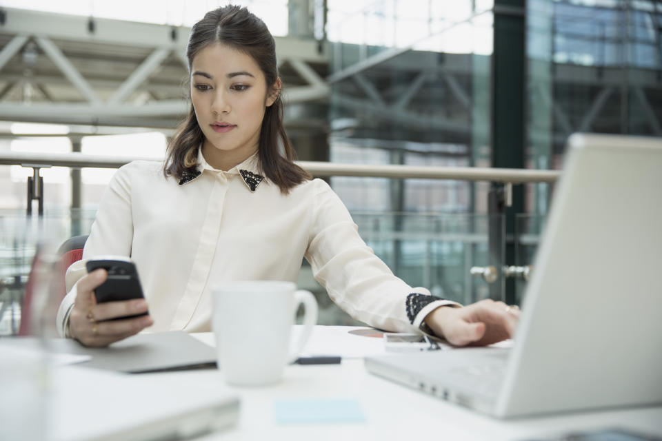 Businesswoman using laptop and texting with cell phone in conference room