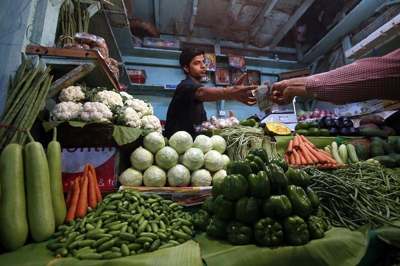 A vendor accepts money from a customer at his vegetable stall at a wholesale fruit and vegetable market in Mumbai