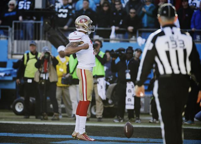 San Francisco 49ers quarterback Colin Kaepernick (7) celebrates after scoring a touchdown against the Carolina Panthers during the second half of a divisional playoff NFL football game, Sunday, Jan. 12, 2014, in Charlotte, N.C. (AP Photo/John Bazemore)