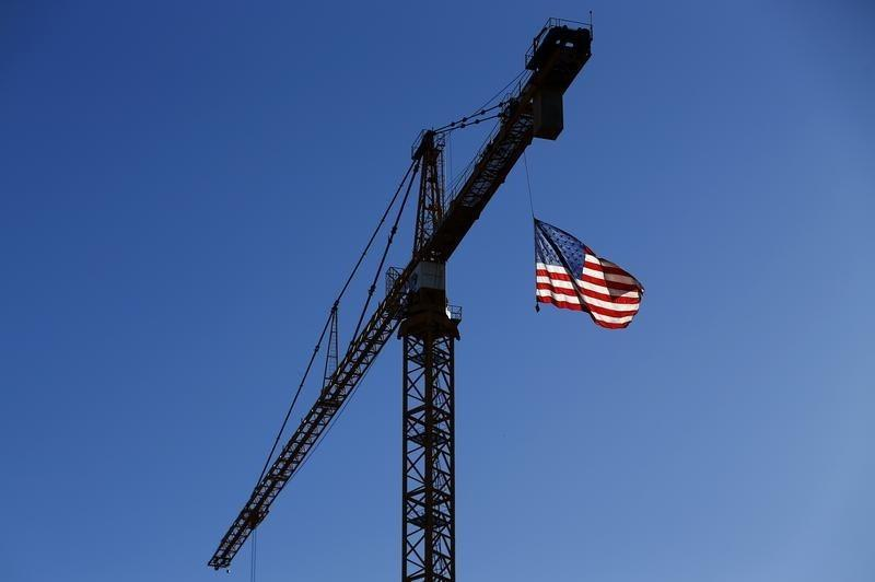 A crane flies an American flag over a construction site in downtown Los Angeles
