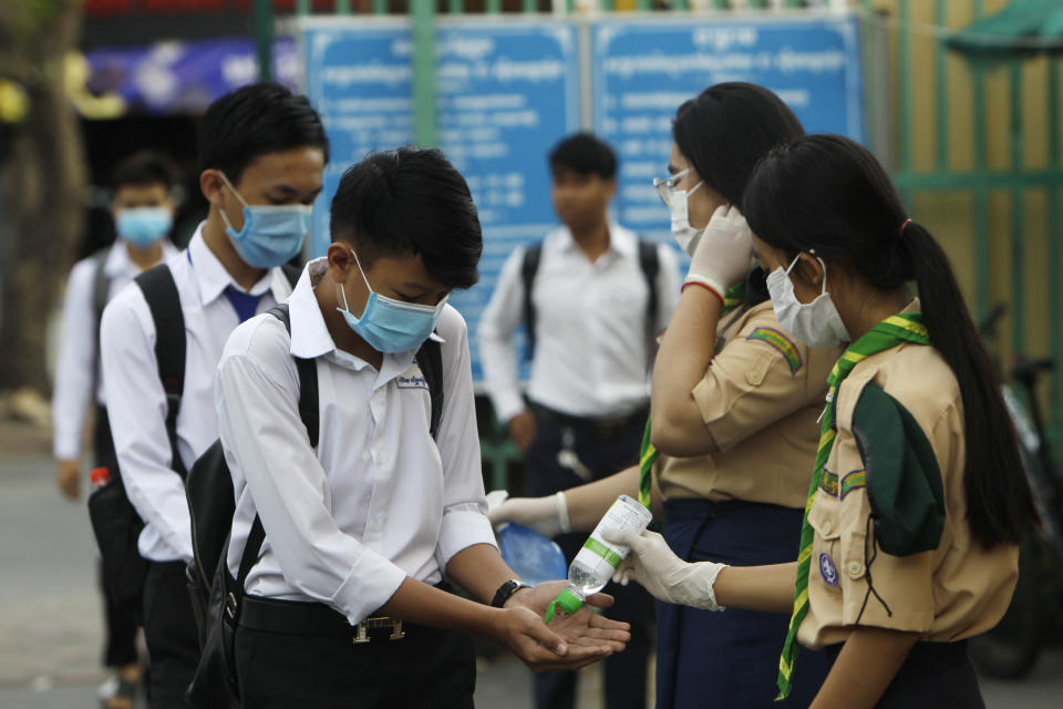 Students disinfect their hands to avoid the contact of coronavirus before their morning class at Santhormok high school, in Phnom Penh, Cambodia, Monday, Nov. 2, 2020. Schools throughout Cambodia that had been shut in March because of the coronavirus crisis reopened Monday, but with limits on class sizes and hours. (AP Photo/Heng Sinith)