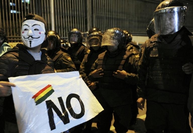 A supporter of Bolivia's presidential candidate Carlos Mesa in front of riot police during a protest over the disputed vote count (AFP Photo/JORGE BERNAL)