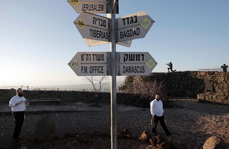 Israelis walk near a sign for tourists showing the distance to Damascus and Baghdad at an army post on Mount Bental in the Israeli-annexed Golan Heights (AFP Photo/Jalaa Marey)