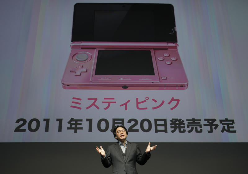 Nintendo President Satoru Iwata, standing in front of an image of a pink-color model of the 3DS portable to woo women users, speaks during a news conference at a convention center  in Tokyo, Japan, Tuesday, Sept. 13, 2011. Nintendo is readying an array of video games for the holidays in an aggressive attempt at catch-up for lost time from the sales delay of the 3DS portable machine last year. (AP Photo/Itsuo Inouye)