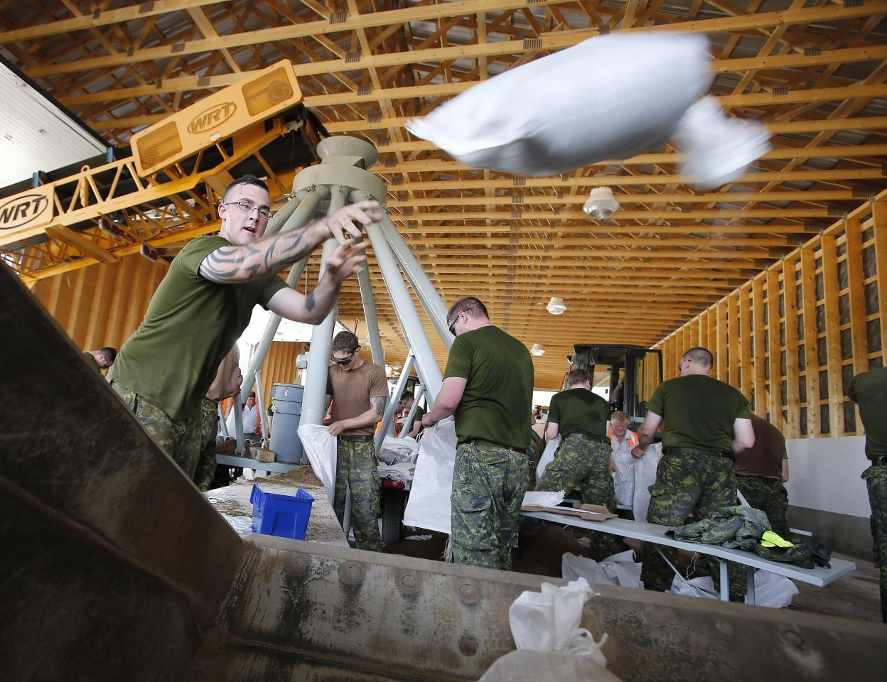 Bombardier Jonathan Kaiser and others work to fill and load sandbags in Portage La Prairie, Manitoba, Saturday, July 5, 2014. Tropical storm Arthur hit Canada's Maritime provinces with near-hurricane strength winds and torrential rains, knocking out power to nearly 200,000 customers. (AP Photo/The Canadian Press, John Woods)