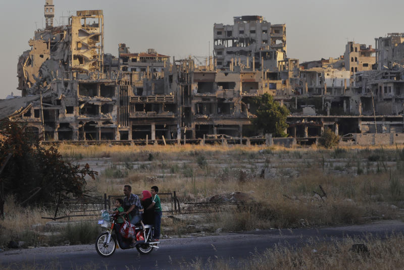FILE - In this Aug. 15, 2018 file photo, people ride their motorcycle by damaged buildings in the old town of Homs, Syria.   Syrian government forces came under separate attacks from Islamic State militants and al-Qaida-linked insurgents in different parts of the country that killed nearly 50 soldiers and allied fighters, activists and a war monitoring group said Saturday, April 20, 2019.  In one attack, IS militants ambushed Syrian government forces in the desert of central Homs province Thursday night, setting off two days of clashes that killed 27 soldiers, including four officers, the Syrian Observatory for Human Rights said.(AP Photo/Sergei Grits)