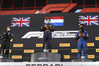 From left, second placed Mercedes Lewis Hamilton, first placed Red Bull's Max Verstappen and third placed McLaren's Lando Norris celebrate on the podium at the end of the Emilia Romagna Formula One Grand Prix, at the Imola racetrack, Italy, Sunday, April 18, 2021. (Bryn Lennon/ Pool Via AP)