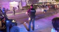 In this image taken from video, SWAT officers in bulletproof vests disperse pepper spray balls on Saturday evening, March 20, 2021, to break up rowdy, spring break crowds that descended on Miami's South Beach by the thousands, trashing restaurants and flooding the streets without masks or social distancing despite COVID-19 restrictions. After days of partying and confrontations between police and large crowds, Miami Beach officials have ordered an emergency curfew. (WPLG via AP)