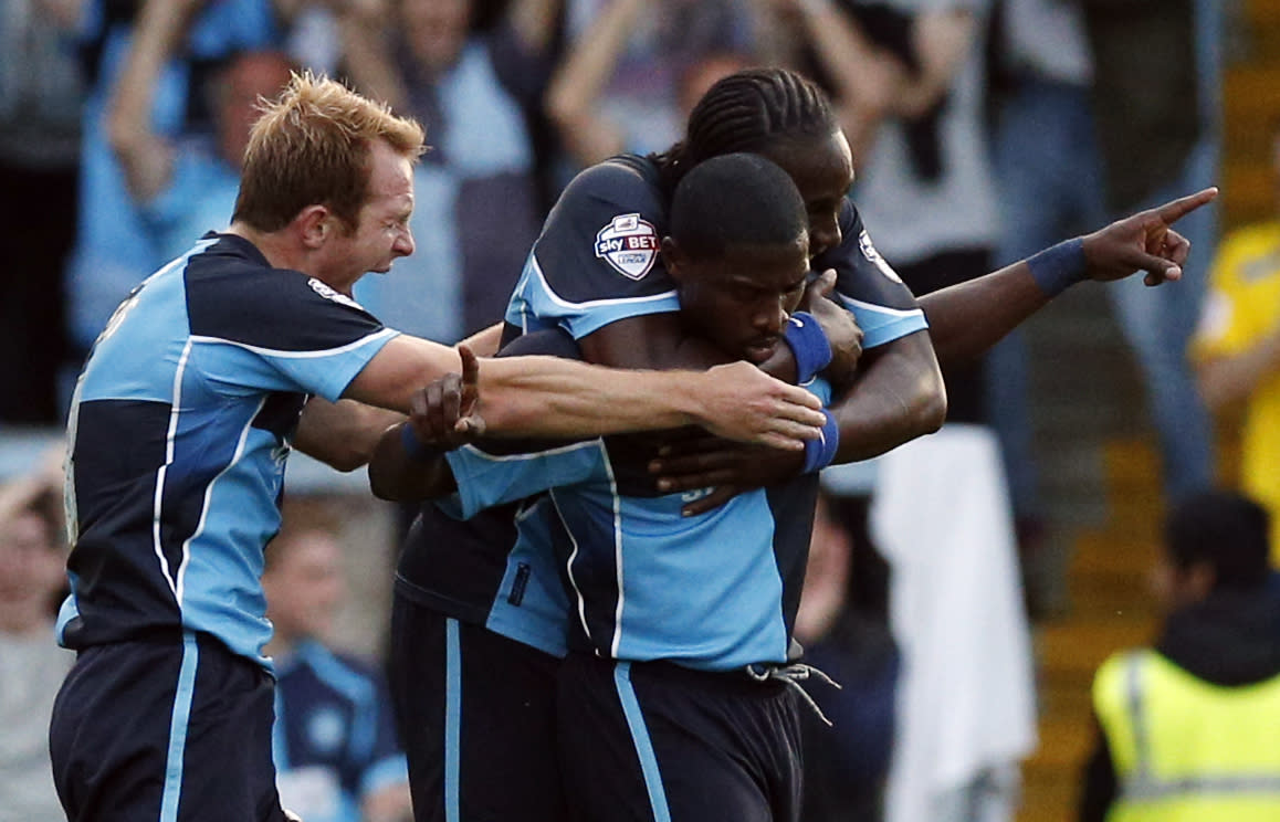 Wycombe's Jo Kuffour (centre) celebrates scoring the equalising goal with team-mates Marvin McCoy (right) and Stuart Lewis during the Capital One Cup, First Round match at Adams Park, Wycombe.