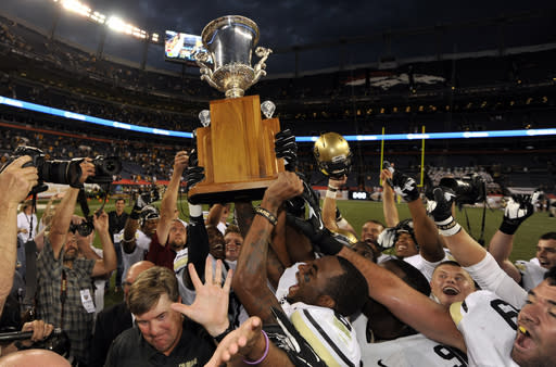 Colorado team members hoist the Rocky Mountain Showdown cup as they celebrate their 41-27 victory over Colorado State during an NCAA college football game ,Sunday Sept. 1, 2013, in Denver. (AP Photo/Jack Dempsey)