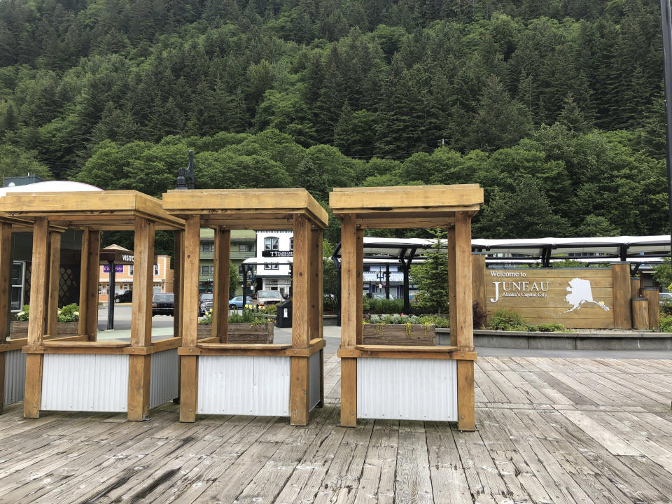Stalls that during typical summers are filled with workers offering shore-side excursions to cruise ship passengers stand empty Monday, June 15, 2020, in Juneau, Alaska. Tourism is one of the main drivers of the Alaska economy, which means some businesses are suffering during the pandemic. (AP Photo/Becky Bohrer)