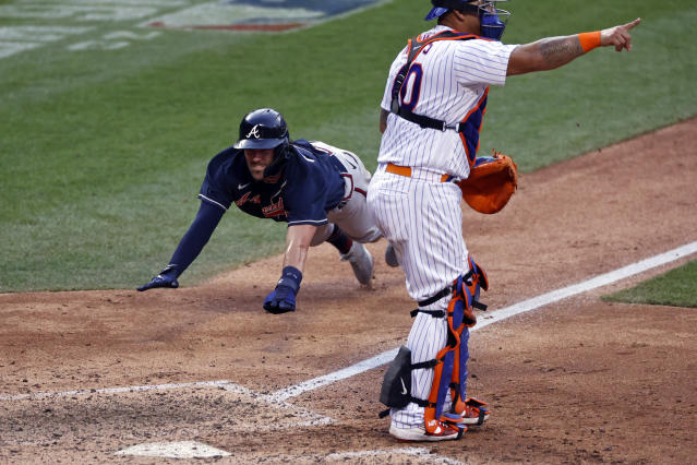 Atlanta Braves' Dansby Swanson, left, scores a run behind New York Mets catcher Wilson Ramos during the 10th inning of a baseball game Saturday, July 25, 2020, in New York. (AP Photo/Adam Hunger)