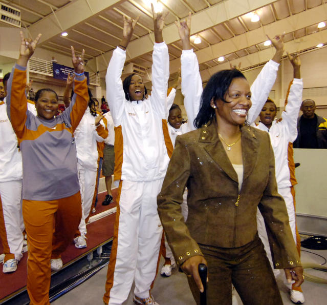 FILe - In this March 11, 2006, file photo, Texas women's coach Bev Kearney, front right, leads the team to accept their national championship trophy at the NCAA Division I Indoor track and field championships in Fayetteville, Ark. The University of Texas has agreed to settle a race and sexual discrimination lawsuit filed by former women's track coach Bev Kearney. Kearney attorney Jody Mask on Wednesday, Jun 20, 2018, told The Associated Press that the case will be dismissed. University spokesman Gary Susswein confirmed the school agreed to settle. Terms were not immediately disclosed. (AP Photo/April L. Brown, FIle)