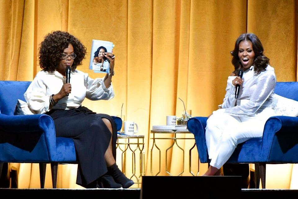 """Michelle Obama, right, appears with Oprah Winfrey to discusses her book """"Becoming"""" during her book tour in Chicago on Nov. 14, 2018. Penguin Random House announced Wednesday that the former first lady's multimillion-selling memoir will be released in a young readers edition and also will  be coming out as a paperback, more than two years after it was first published."""