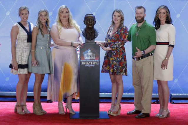 FILE - In this Aug. 3, 2019, file photo, members of the Bowlen family, from left to right, Brittany Bowlen, Annabel Bowlen, Amie Bowlen Klemmer, Christina Bowlen, Patrick Bowlen and Beth Bowlen Wallace pose with a bust of former Denver Broncos owner Pat Bowlen during the induction ceremony at the Pro Football Hall of Fame in Canton, Ohio. Pat Bowlen's two oldest daughters, Wallace and Klemmer, have put themselves at risk of being disinherited by challenging their father's trust, which is in charge of selecting the next controlling owner of the Broncos, a franchise valued at more than $2.5 billion. (AP Photo/Ron Schwane, File)