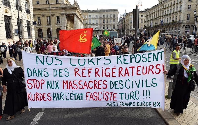 """Members of the Kurdish community in Bordeaux walk behind a banner reading """"Our bodies lie in refrigerators! Stop the massacre of Kurdish civilians by the Turkish fascist state!"""" during a demonstration on October 10, 2015 (AFP Photo/Mehdi Fedouach)"""