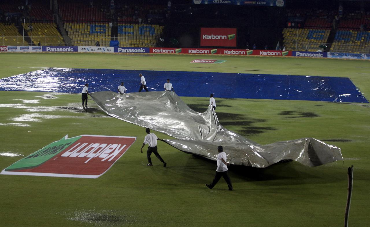 Ground staff rush to cover the field as it starts raining during the CLT20 match between Titans and Trinidad & Tobago at Sardar Patel Stadium, Motera in Ahmedabad on Sept. 30, 2013. (Photo: IANS)