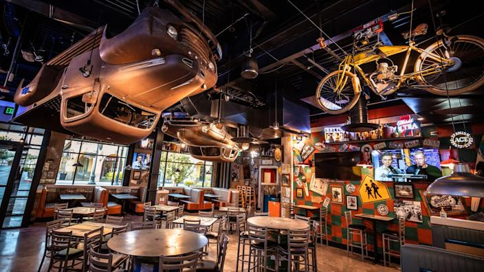 The interior of Sickies Garage, which has vintage pickup trucks and motorcycles hanging from the ceiling
