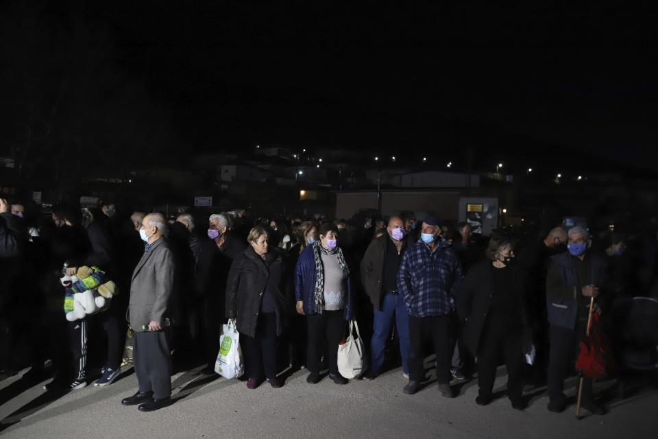 Local residents wait for a bus which will transfer them to hotels after an earthquake in Damasi village, central Greece, Wednesday, March 3, 2021. An earthquake with a preliminary magnitude of at least 6.0 struck central Greece Wednesday and was also felt in neighboring Albania and North Macedonia, and as far as Kosovo and Montenegro. (AP Photo/Vaggelis Kousioras)