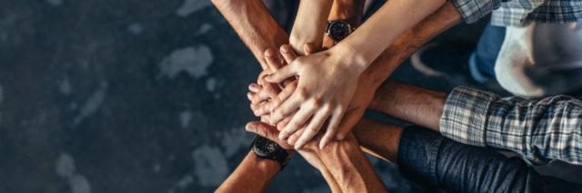 A group of people with their hands in exhibiting team work.