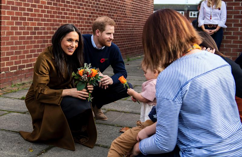 Bonnie and Maggie Emanuel give a posy of flowers to Meghan during a visit at Broom Farm Community Centre in Windsor on Nov. 6. (Photo: Handout . / Reuters)