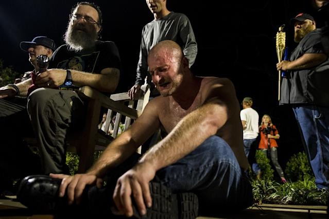 <p>A man cringes after being hit in the face with pepper spray during a clash between counter protestors and Neo Nazis, Alt-Right, and White Supremacist groups after they marched through the University of Virginia Campus with torches in Charlottesville, Va., on Aug. 11, 2017. (Photo: Samuel Corum/Anadolu Agency/Getty Images) </p>