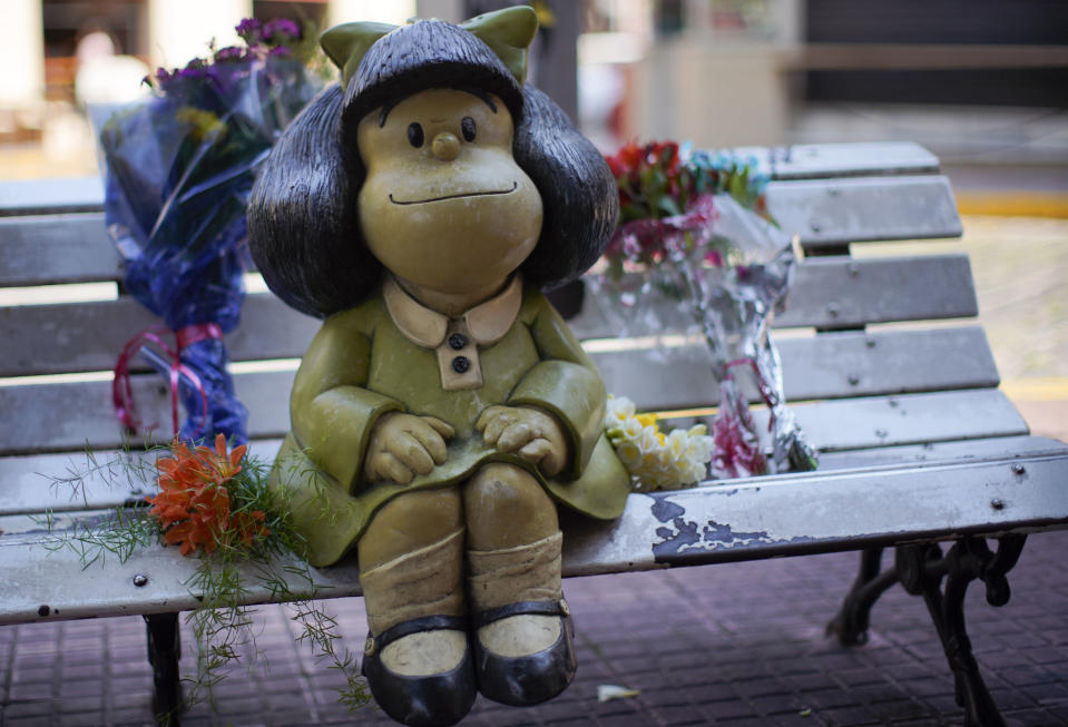 Flower bouquets flank a statue of the comic strip character Mafalda created by Argentine cartoonist Joaquin Salvador Lavado, who was better known as Quino, in Buenos Aires, Argentina, Wednesday, Sept. 30, 2020. Lavado passed away on Wednesday, according to his editor Daniel Divinsky who announced it on social media. He was 88. (AP Photo/Victor R. Caivano)
