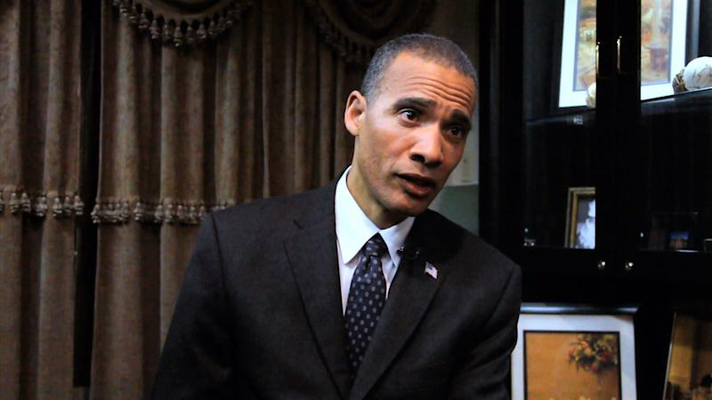 """In this image from video, President Barack Obama lookalike Larry Graves speaks during an interview. Graves has the security detail, the prominent ears and the U.S. flag pin, but substitute teacher Graves is no Barack Obama. He's a professional lookalike for the president. They have something else in common, too: a frantic schedule leading up to the inauguration. """"It's definitely a busy time,"""" Graves said. """"Between the campaign season and the inauguration, it's been prime time. Barack Obama is a respectable guy. People want to have him at their parties."""" (AP Photo)"""