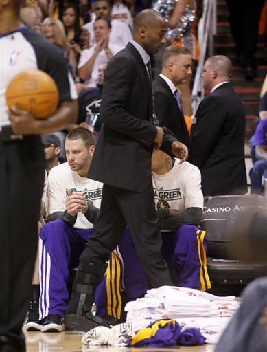 Los Angeles Lakers' Kobe Bryant walks back to the bench during the second half of an NBA basketball game against the Phoneix Suns, Saturday, April 7, 2012, in Phoenix. (AP Photo/Matt York)