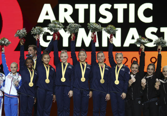 Team U.S.A. celebrates winning the gold medal in the women's team final at the Gymnastics World Championships in Stuttgart, Germany, Tuesday, Oct. 8, 2019. Left is team Russia, silver medal, and right is team Italy, bronze medal. (AP Photo/Matthias Schrader)