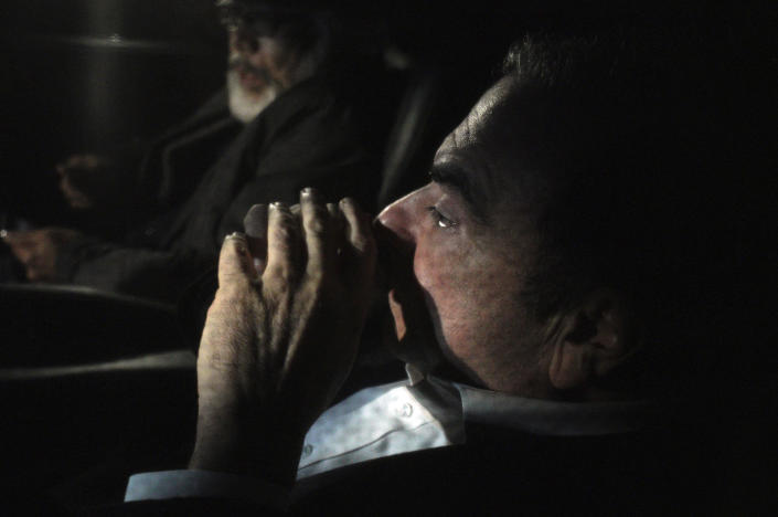 Former Nissan chairman Carlos Ghosn, front, travels in a car Wednesday, March 6, 2019, in Tokyo, after posting 1 billion yen ($8.9 million) in bail once an appeal by prosecutors against his release was rejected. Ghosn was arrested in November and is charged with falsifying financial reports and breach of trust. (AP Photo/Eugene Hoshiko)