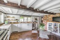 <p>We love this traditional kitchen, which has white cabinets, wooden flooring and gorgeous exposed beams. </p>