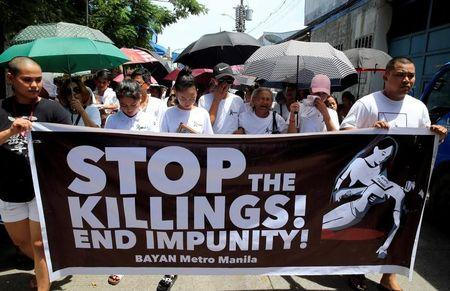 FILE PHOTO: Relatives and loved ones of Leover Miranda hold a streamer calling to stop the continuing rise of killings uring a funeral march at the north cemetery in metro Manila
