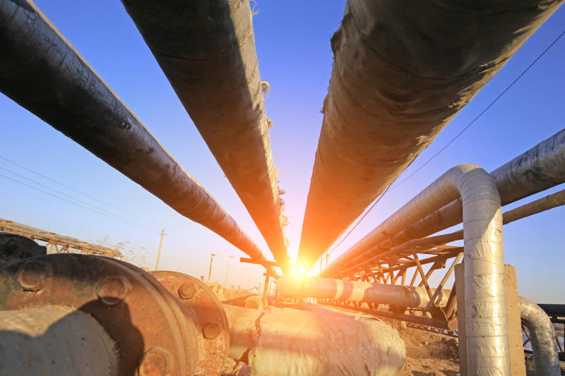 Several pipelines with the sun shining brightly.