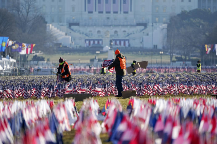 Workers begin to remove a display of flags on the National Mall one day after the inauguration of President Joe Biden, Thursday, Jan. 21, 2021, in Washington. (AP Photo/Julio Cortez)