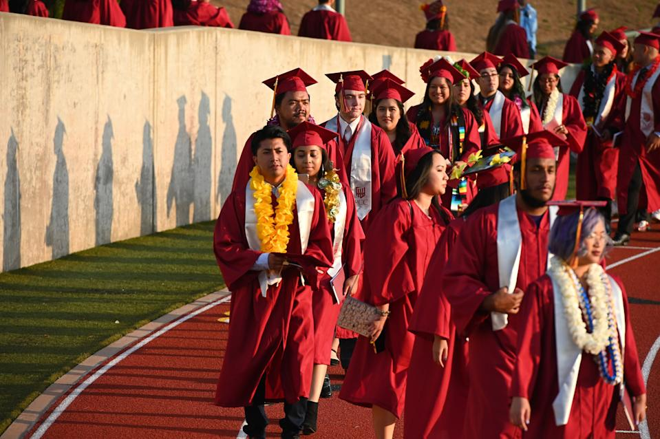 """Students earning degrees at Pasadena City College participate in the graduation ceremony, June 14, 2019, in Pasadena, California. - With 45 million borrowers owing $1.5 trillion, the student debt crisis in the United States has exploded in recent years and has become a key electoral issue in the run-up to the 2020 presidential elections. """"Somebody who graduates from a public university this year is expected to have over $35,000 in student loan debt on average,"""" said Cody Hounanian, program director of Student Debt Crisis, a California NGO that assists students and is fighting for reforms. (Photo by Robyn Beck / AFP)        (Photo credit should read ROBYN BECK/AFP/Getty Images)"""
