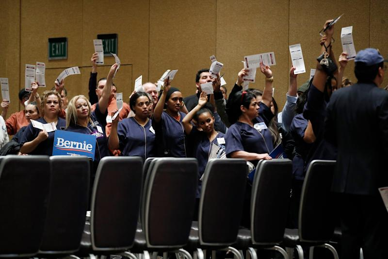 Casino workers hold up presidential preference cards as they support Democratic presidential candidate Sen. Bernie Sanders, I-Vt., during a presidential caucus at the Bellagio hotel-casino on Saturday.