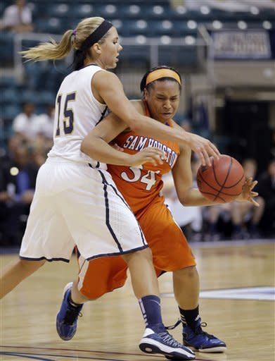 Sam Houston State's Chanice Smith (34) is fouled by Oral Roberts' Kevi Luper (15) during the second half of an NCAA college basketball game for the Southland Conference women's tournament title, Saturday, March 16, 2013, in Katy, Texas. Oral Roberts won 72-66. (AP Photo/David J. Phillip)