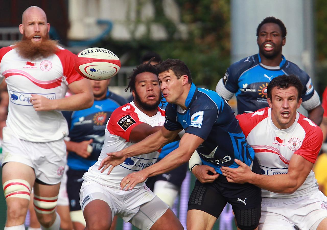 Montpellier's Anthony Floch, center right, is tackled by Biarritz's Damien Traille, right, as Biarritz's Erik Lund, left, looks on during their French Top 14 rugby union match at the Stade Aguilera, in Biarritz, southwestern France, Saturday Aug. 24, 2013. (AP Photo/Bob Edme)
