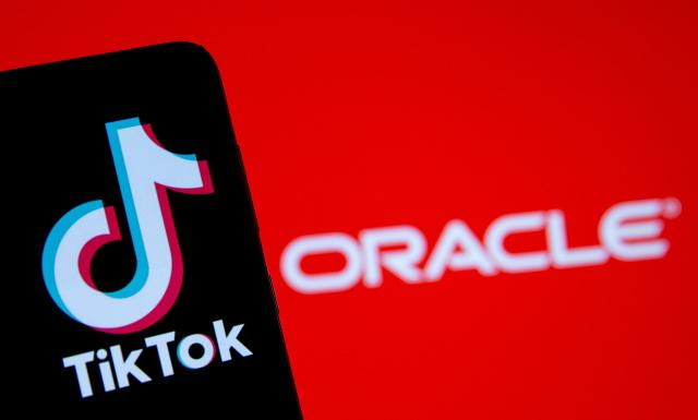 A smartphone with the Tik Tok logo is seen in front of a displayed Oracle logo in this illustration taken, Septemeber 14, 2020. REUTERS/Dado Ruvic/Illustration - RC27YI9D74SH