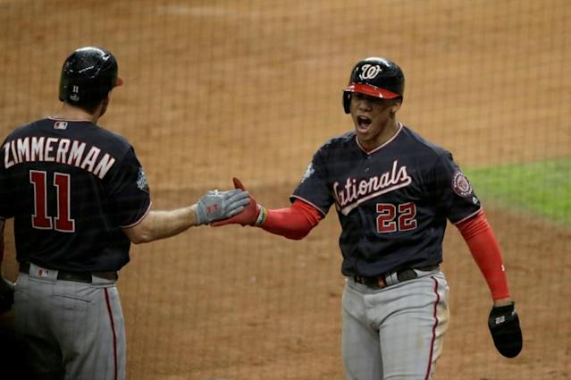 Juan Soto, right, and Ryan Zimmerman celebrate a home run by Howie Kendrick that put Washington ahead to stay in a 6-2 victory Wednesday over Houston that brought the Nationals the World Series title (AFP Photo/Bob Levey)