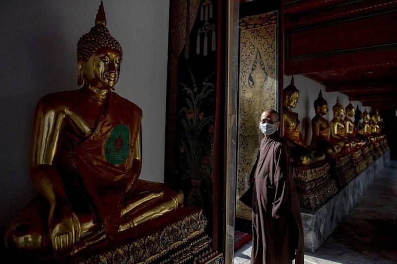 a Buddhist monk from Vietnam wearing a face mask walks amid Buddhist statues at Wat Pho in Bangkok, Thailand. Image credit: AP