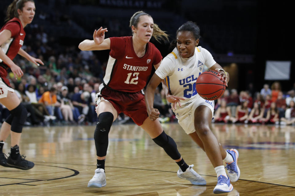 UCLA's Charisma Osborne (20) drives around Stanford's Lexie Hull (12) during the second half of an NCAA college basketball game in the semifinal round of the Pac-12 women's tournament Saturday, March 7, 2020, in Las Vegas. (AP Photo/John Locher)