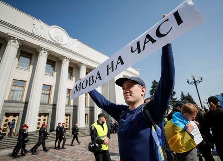 "An activist attends a rally to demand lawmakers vote for a law that grants special status to the Ukrainian language and introduces mandatory language requirements for public sector workers, in front of the parliament building in Kiev, Ukraine April 25, 2019. The banner reads ""High time for the language"".  REUTERS/Gleb Garanich"