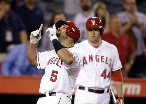 Los Angeles Angels' Albert Pujols celebrates his home run against the Baltimore Orioles as teammate Mark Trumbo, rear right, watches during the ninth inning of a baseball game in Anaheim, Calif., Thursday, May 2, 2013. The Orioles won 5-1. (AP Photo/Jae C. Hong)