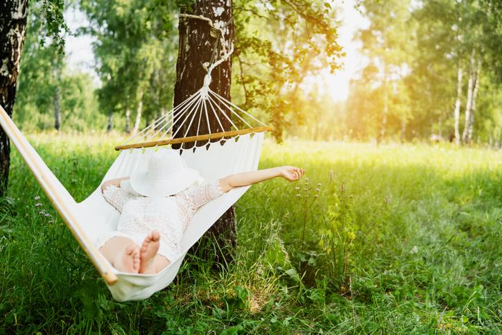 A person in a hammock in the woods.