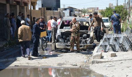 Iraqi people with security forces walk near a burnt vehicle at the site of an attack in Tikrit