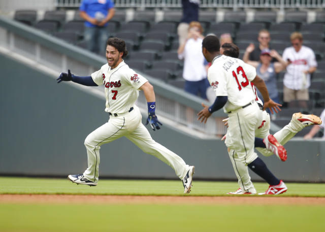 Atlanta Braves Dansby Swanson is chased by teammates after hitting a game winning, two run single in the ninth inning of a baseball game against the Miami Marlins, Sunday, May 20, 2018, in Atlanta. The Atlanta Braves won the game 10-9. (AP Photo/Todd Kirkland)